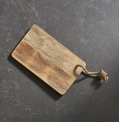 Empty cutting board with cloth napkin on a stone dark surface