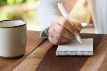 Paper note.Woman hand writing note with white pen on wooden table early in the morning ,front view.