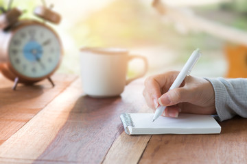 Paper note.Woman hand writing note with white pen on wooden table at sunset ,blurred alarm clock and coffee cup in background.