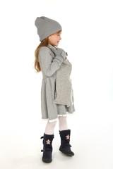 Kleines Mädchen in Winterkleidung schaut in eine Richtung und lacht