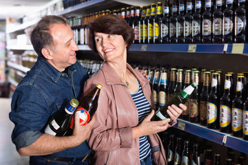 Husband and wife selecting a beer at  store