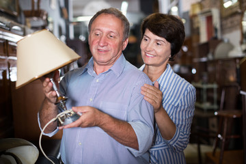 Smiling adult woman with her husband are buying antique lamp
