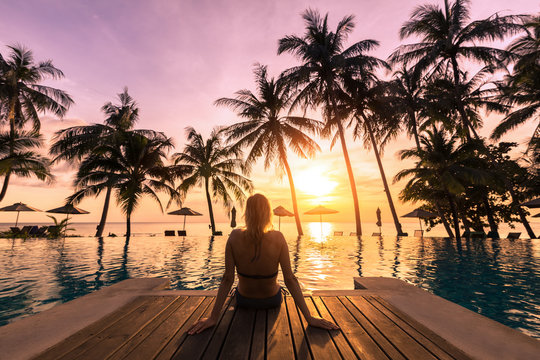 Woman relaxing by the pool in luxurious beachfront hotel resort