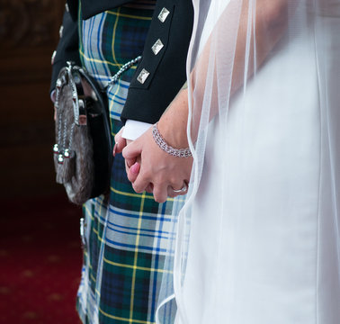 Scottish wedding ceremony with groom wearing kilt and sporran whilst holding hands with bride