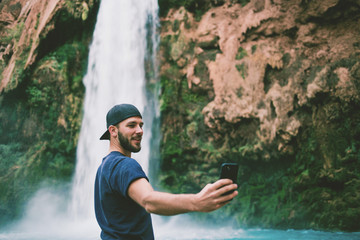 Man taking a cell phone picture  in front of beautiful blue waterfall