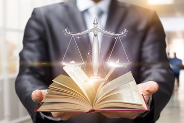 Lawyer shows the book and scales of justice .
