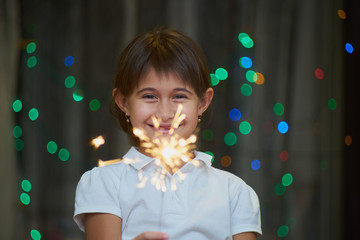 Little girl with sparkler on blurred bokeh backgroundIndoor New Year photography
