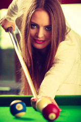 Young fashionable girl playing billiard.