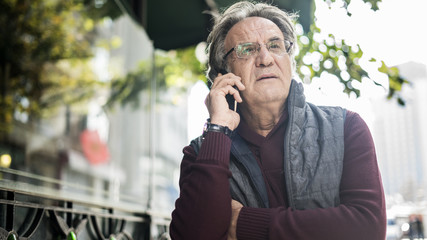 Senior man talking phone in outdoors