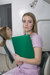 A young dentist girl holding a green folder on the background dental office.In the chair sits a patient