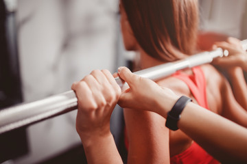 Squats with a barbell, coach helps girl crouch with barbell on her shoulders.