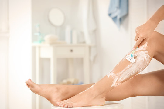 Beautiful woman shaving her legs in bathroom