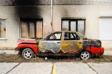 Burnt red car after fire accident