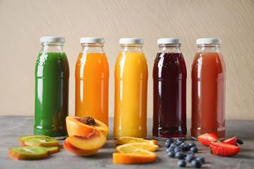 Bottles with fruit juices on table against light wall