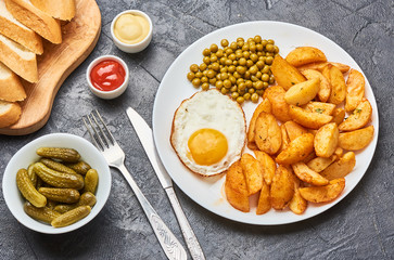 Fried potatoes with fried eggs, green peas on concrete gray background