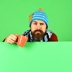 Hipster with confused face has warm tea or coffee