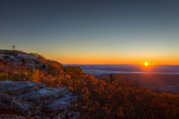 Standing man in distance silhouette far away on autumn morning in Bear Rocks, West Virginia looking at sunrise