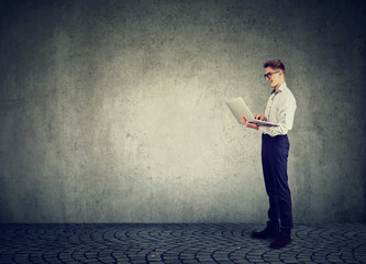 Business man using his laptop computer standing along concrete wall with blank copy space