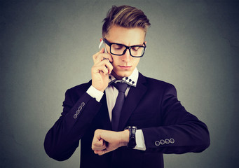 Business and time management concept. Businessman looking at wrist watch, talking on mobile phone.