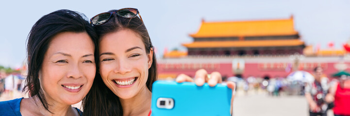 Asia travel selfie in China. Chinese women tourists taking self-portrait phone photo at Tiananmen Square Beijing vacation. Summer vacation banner panorama.