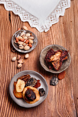 Dried fruits and nuts in pottery bowls on old wooden table