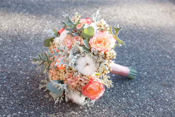 Coral and peach bridal bouquet isolated on grey background