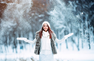 Girl in white catching snowflakes