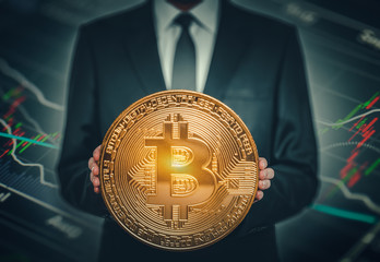 businessman holding big shiny bitcoin in hands in front of stock market data chart background