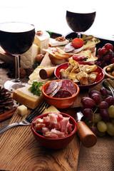 Italian antipasti wine snacks variety set. Cheese, Mediterranean olives, pickles, Prosciutto di Parma, tomatoes, artichokes and wine in glasses. Spanish tapas