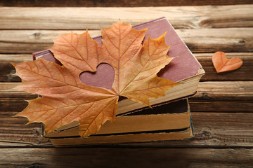 Dry maple leaf with heart and old books on brown wooden table