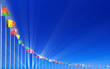 Flags and sunbeams against blue sky, copyspace
