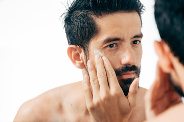 Handsome man applying facial cream in bathroom while looking at mirror