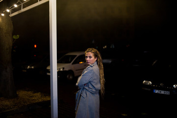 Girl with dreadlocks walking at night street of city.