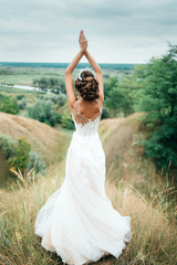 A young girl, the bride in a wedding dress, is turned her back and staring into the distance on the river and a beautiful landscape. Beauty wedding hairstyle. Bride. Beautiful hairstyle rear view.