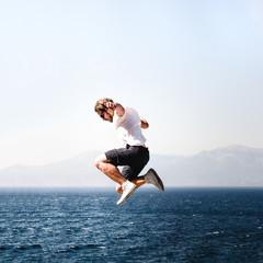 Mann in weißem T-Shirt spring über das weite Meer