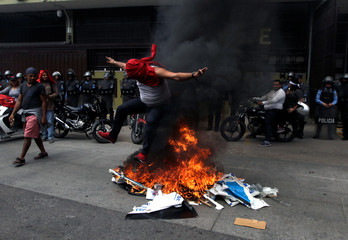 Supporter of Nasralla  jumps on burning images of current Honduras president Hernandez as he waits for official presidential election results in Tegucigalpa
