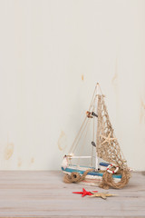 Miniature boat, starfish and seashells stand on a gray background. Marine lifetime.