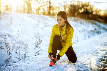 Stores à enrouleur Glisse hiver Young sportive healthy focused girl tying shoelaces in winter sportswear on snowy winter road with earphones in the sunny morning.