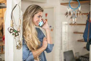 Beautiful young woman in a hipster kitchen talks to her phone dressed in a jeans shirt and a white shirt