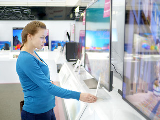 Woman buying TV in a store.