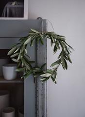 kleiner Kranz aus Olivenzweigen hängt an Schrank im Advent