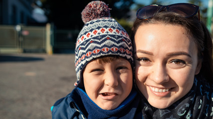 Young boy and a young woman are makes faces and smiling in a park in the winter on a sunny day