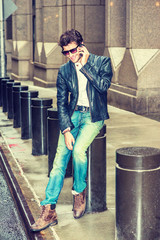 Wearing black leather jacket, blue jeans, wearing sunglasses, young European Business Man with beard sitting on street in New York, talking on mobile phone during working break. Color filtered effect