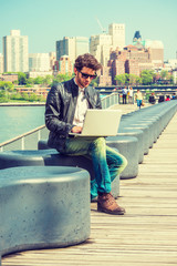 European businessman traveling, working in New York. Wearing black leather jacket, blue jeans, brown boot shoes, sunglasses, a guy with beard, sitting on bench at harbor, working on laptop computer.