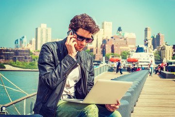 Businessman traveling, working in New York. Wearing sunglasses, a young guy with beard, sitting on bench at harbor, working on laptop computer, talking on phone in the same time. .