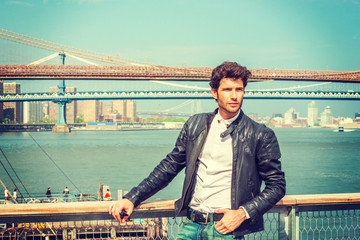 European businessman traveling in New York. Wearing black leather jacket, white shirt, a young guy with beard, standing at harbor, looking around, thinking. Manhattan, Brooklyn bridges on background..