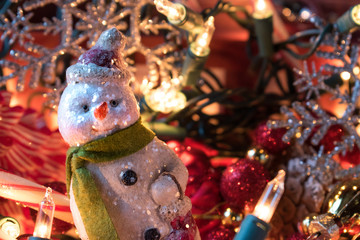 Christmas snowman ornament with decorations and lights closeup