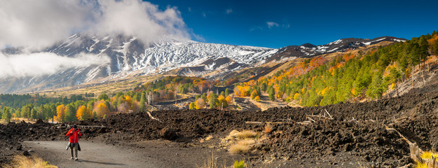 Mount Etna, Italy: panorama of the northern side of the volcano and a hiker walking on a lavic pathway Fototapete