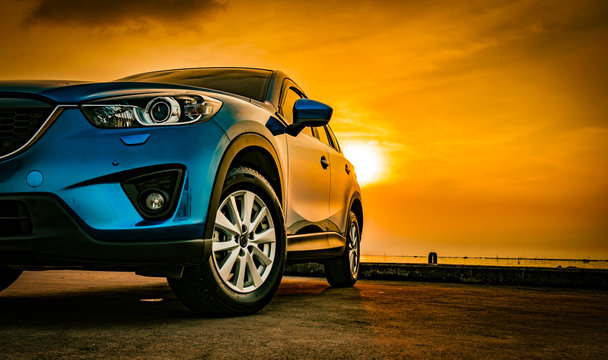 Blue compact SUV car with sport and modern design parked on concrete road by sea beach at sunset. New shiny SUV car drive for travel on summer vacations with road trip. Front view of electric car.