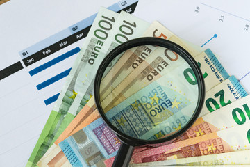 Magnifying glass on pile of Euro banknotes with printed quarter chart graph as Euro economy or debt analysis concept